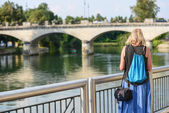 A blonde woman at the river bank facing the big bridge over the  — Stock Photo