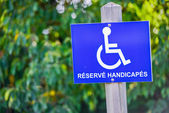 Wheelchair handicap sign fastened on a wooden pole — Stock Photo
