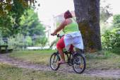 Overweight woman riding on a bicycle in a park — Stock Photo