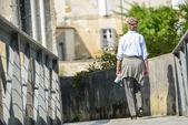 An elderly woman walking along narrow passage  — Stock Photo