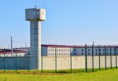 Prison area with a tall watchtower surrounded with fence — Stock Photo