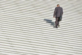 A man climbing up along large endless stair — Stock Photo