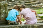 Two kids playing on the ground next to a mossy stone — Stock Photo