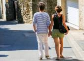A young couple walking in the old narrow downtown street — Stock Photo