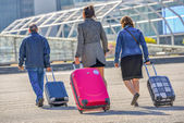 Three people pulling their luggage towards airport entrance — Stock Photo