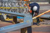 A construction worker drilling halls in metal piece — Stock Photo
