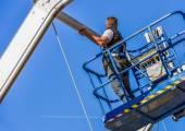 Construction worker fastening roof ridge on skylift — Stock Photo