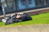 A man sleeping on a green loan outdoors — Stock Photo