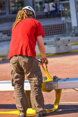 A construction worker with long dreadlocks fastening a yellow ho — Stock Photo