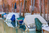 Boats with tarpaulin in romantic narrow canal in Venice. — Stock fotografie