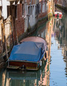 Boats with tarpaulin in romantic narrow canal in Venice. — Stockfoto
