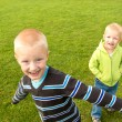 Happy children (boys, brothers) playing on green grass — Stock Photo #71707299
