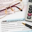 Tax form with pen, calculator, and glasses taxation concept — Stock Photo #58629381