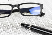 Finance report analysis with pen, and glasses — Foto de Stock