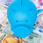 Blue piggy bank on international banknote background  — Stock Photo #60228219