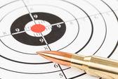 Rifle bullet over target background  — Stockfoto