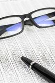Pióra i okulary odpoczynku na cenę akcji szczegółowy dziennik finansowy — Zdjęcie stockowe