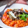 Tomato risotto, red rice with fried chicken liver, onions, Itali — Stock Photo #67790421