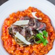 Tomato risotto, red rice with fried chicken liver, onions, Itali — Stock Photo #67790437