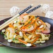 Asian noodles with shrimp, vegetables, carrots, peanuts, onions, — Stock Photo #67791241