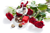 Assorted gourmet chocolate and bouquet red roses  — Stock Photo