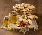 Peanut oil and nuts on a wooden table — Stock Photo