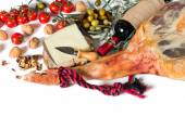 Ham, olives, red wine, cheese, tomatoes and nuts — Stock Photo