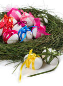Easter composition with eggs, nest and ribbons — Stock Photo