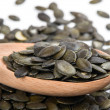 Pumpkin seed in a wooden spoon and forming a background — Stock Photo #65870293