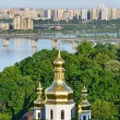 The capital of Ukraine, Kiev. Golden dome of the church, the bridge across the Dnieper River. Beautiful spring cityscape — Stockfoto #74233913