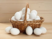 Basket with eggs on a wooden table — Stock Photo