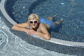 Aged woman is lying prone in blue water of pool. — Stock Photo