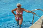 Aged woman is posing in pool water near handrails. — Stock Photo