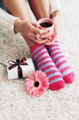 Female legs in socks and coffee — Stockfoto
