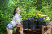 Smiling girl leaned on the stand for flowers in pots — Stock Photo