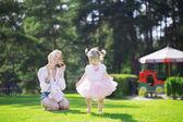 Smiling girl applauds baby — Stock Photo