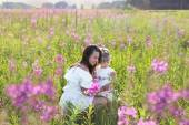 The girl shows the child a flower in a field — Stock Photo