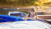 Smiling girl sitting in a boat at sunset — Stock Photo