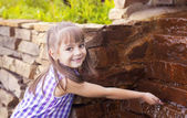 Smiling girl takes water by hand from the Creek — Stock Photo