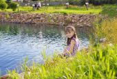 Smiling girl turned around sitting on the Bank of the pond — Stock Photo