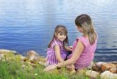 Mother with daughter sitting on the waterfront — Stock Photo