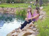 Mother with daughter sitting on the Bank of the pond — Stock Photo