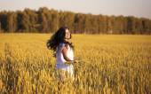 Smiling beautiful girl spinning in a field of wheat with ears — Stock Photo