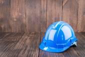 Construction hard hat on wooden background — Stockfoto
