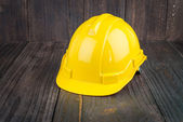 Construction hard hat on wooden background — Stock Photo