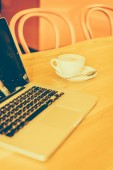 Coffee cup and laptop — Stock Photo