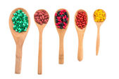 Pill on wooden spoons — Stock Photo