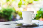 Coffee cup on wooden table — Stock Photo