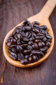 Coffee beans in wooden spoon — Stock Photo