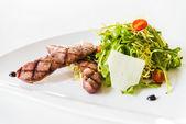 Sausage salad on white dish — Stock Photo